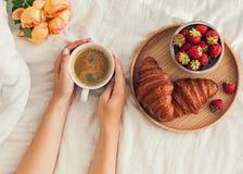 妇女` s递拿着一杯咖啡在床上的与白色床单 免版税图库摄影