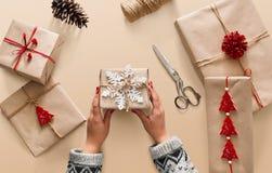 妇女` s递拿着圣诞节假日礼物用雪花装饰 图库摄影