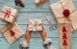 妇女` s递拿着圣诞节假日礼物用雪花装饰 库存照片