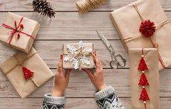妇女` s递拿着圣诞节假日礼物用雪花装饰 免版税库存图片