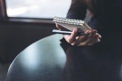 妇女` s递拿着在桌上的一个白色空白的笔记本 免版税图库摄影