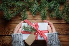妇女` s递拿着在纸白色的文本的圣诞节礼物与红色丝带和空白 与拷贝空间的顶视图 库存图片