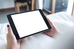 妇女` s递拿着有空白的桌面白色屏幕的黑片剂个人计算机,当坐一张白色床时 图库摄影