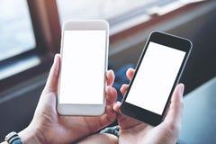 妇女` s递拿着有空白的白色屏幕的两个手机在现代咖啡馆 图库摄影