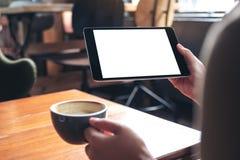 妇女` s递拿着有空白的白色屏幕的黑片剂个人计算机,当喝在木桌上的咖啡在咖啡馆时 免版税库存照片