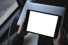 妇女` s递拿着有空白的白色桌面屏幕的黑片剂个人计算机有在桌上的膝上型计算机的在咖啡馆 库存照片