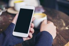 妇女` s递拿着有空白的黑屏幕和一个咖啡杯的白色手机在葡萄酒咖啡馆的木桌上 免版税库存照片