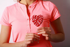 妇女` s递拿着棒棒糖以心脏的形式 礼物为 图库摄影