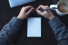 妇女` s递拿着铅笔对写在有膝上型计算机和咖啡杯的一个空白的笔记本在桌上 免版税库存照片