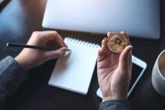 妇女` s递拿着bitcoin和写在有膝上型计算机和手机的空的笔记本在桌上 图库摄影