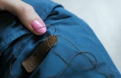 妇女` s递被缝合的皮革插入物到蓝色下来夹克袖子  免版税图库摄影