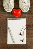 妇女` s鞋子、心脏、笔、黑耳机和白色笔记本f 库存照片