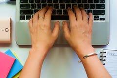 妇女` s顶视图递研究和键入计算机膝上型计算机 免版税图库摄影