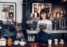 妇女barista接受与片剂的命令,亚洲女性女服务员使用 库存照片