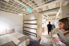 妇女choosinbg卧室家具和床垫 免版税图库摄影