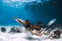 妇女freediver在含沙底部的游泳水中与沙子 图库摄影