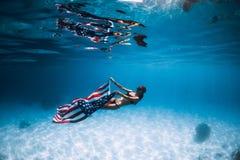 妇女freediver滑动在与美国旗子的含沙海底 库存照片