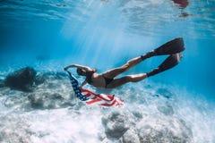 妇女freediver滑动在与美国旗子的含沙海底 图库摄影