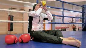 妇女kickboxer在圆环坐并且在训练以后喝水 股票视频