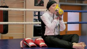 妇女kickboxer在圆环坐并且在训练以后喝水 影视素材