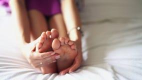 妇女massaga疲乏的他的底部,疼痛脚 影视素材