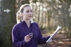 妇女Orienteering在有地图和指南针的森林地 免版税库存照片