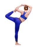 妇女pacticing的国王舞蹈瑜伽姿势的后面看法 免版税库存图片