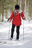 妇女Snowshoeing在森林 免版税库存照片