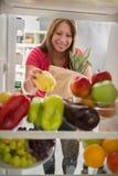 主妇是在市场和被投入的胡椒在冰箱 免版税图库摄影