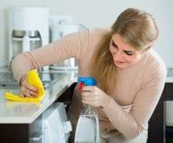 主妇清洁在家庭厨房里 免版税图库摄影