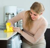 主妇清洁在家庭厨房里 免版税库存图片