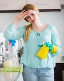 年轻主妇疲乏的打扫灰尘在国内厨房里 免版税图库摄影