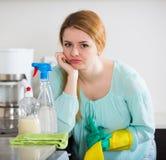 年轻主妇疲乏的打扫灰尘在国内厨房里 图库摄影