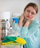 年轻主妇疲乏的打扫灰尘在国内厨房里 免版税库存图片