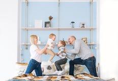 妈咪、爸爸和两个孩子获得在床上的乐趣 所有它是快乐的 库存图片