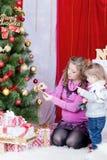 妈咪和女儿装饰圣诞树 库存图片