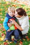 年轻妈咪和她的一起拥抱在秋天公园的小孩儿子 免版税图库摄影