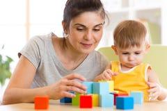 年轻妈咪和她的孩子使用与立方体玩具在托儿所 库存图片