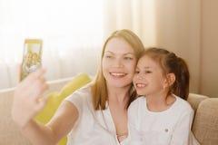 妈咪和她逗人喜爱的女儿儿童女孩使用,微笑着并且拥抱 愉快的Mother& x27; s天 库存照片
