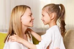 妈咪和她逗人喜爱的女儿儿童女孩使用,微笑着并且拥抱 库存照片