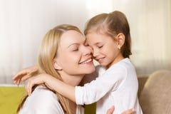 妈咪和她逗人喜爱的女儿儿童女孩使用,微笑着并且拥抱 免版税库存图片