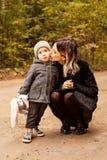 妈咪在森林轻轻地亲吻她的道路的小儿子 免版税库存照片