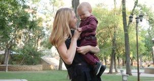 妈咪痒感和使用与她的儿子,笑在母亲的手上的婴孩 股票录像