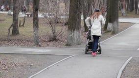 妈咪走与婴儿推车的孩子通过春天胡同 股票视频