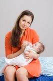 妈咪从瓶六个月女儿哺养坐床 免版税图库摄影