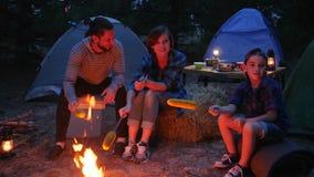 妈妈、儿子和爸爸在森林,在火附近的美国家庭里烤在串串起的玉米,与帐篷的旅行,野餐 股票录像