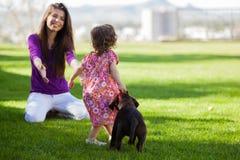 妈妈、女孩和小狗在公园 免版税库存图片
