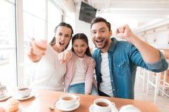 妈妈、爸爸和小女儿为在咖啡馆的一台照相机摆在 免版税图库摄影