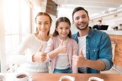 妈妈、爸爸和小女儿为在咖啡馆的一台照相机摆在 图库摄影