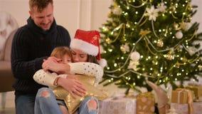 妈妈、爸爸和小小女儿 爱恋的家庭圣诞快乐和新年快乐 快乐的俏丽的人民 父项 影视素材
